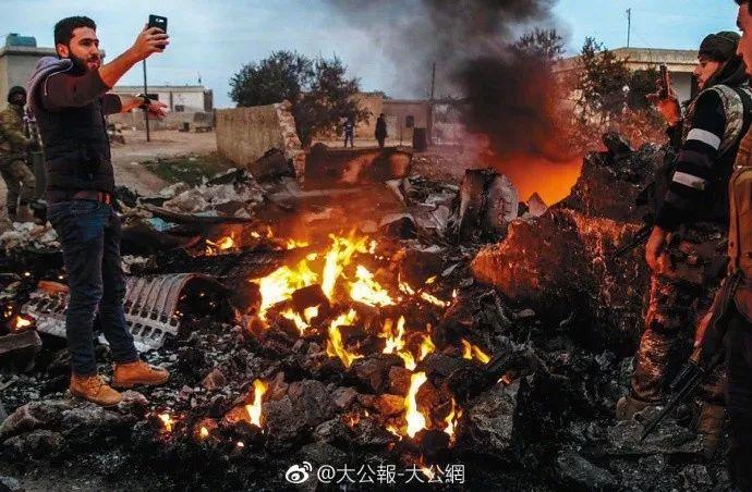 ▲战机坠落后,叙反对派赶到现场站在残骸旁自拍。(香港《大公报》微博)