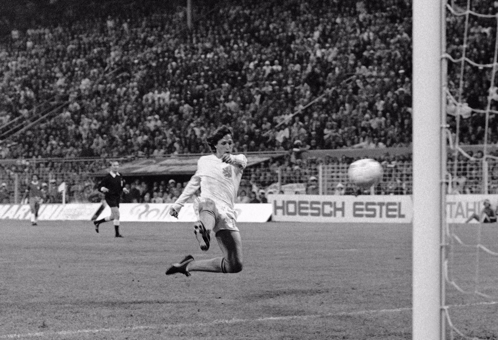 """克鲁伊夫被称为""""荷兰飞人"""",在1974年帮助荷兰打进了世界杯决赛获得亚军,当选本届世界杯的最佳球员。曾经三次荣膺欧洲足球先生称号。他在荷兰的阿贾克斯俱乐部开始自己的职业足球生涯,并在西甲巴塞罗那队达到了顶峰。克鲁伊夫退役后在1988至1996年间担任巴萨主教练。他打造了著名的""""梦之队"""",带领巴塞罗那队夺得1992年欧洲冠军杯冠军,并且从1991年至1994年夺得西甲联赛四连冠。\\\\r\\\\n图为1974年7月4日,荷兰队球员克鲁伊夫(前)在第十届世界杯对阵巴西队的比赛中攻入一球。"""
