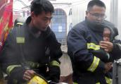 开封一店铺起火后父子被困 消防员裹着仨月大婴儿出火场