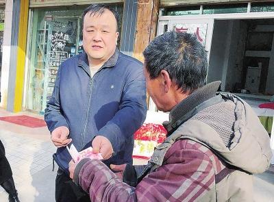 除了米面油,周小力(左一)还给每个贫困户塞了200元钱。