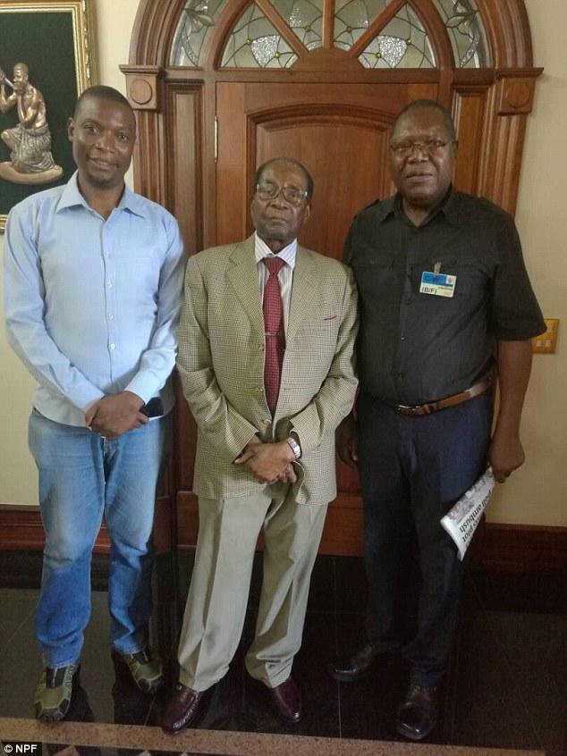 穆加贝(中)与反对党领袖安布罗斯・穆廷希里(右)的合影。(图片来源:《每日邮报》)